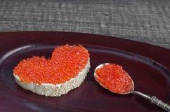 Skjuta in med den röda kaviaren i form av hjärta på ett trämagasin Parallella produkter Royaltyfri Foto