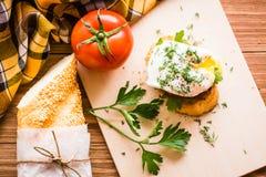 Skjuta in med det tjuvjagad ägget, tomaten, bagetten och persilja på en skärbräda Royaltyfria Bilder