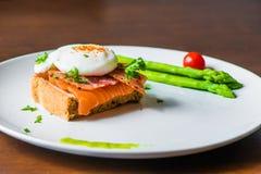 Skjuta in med det tjuvjagade ägget, parma skinka och laxen Arkivbild