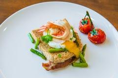 Skjuta in med det tjuvjagade ägget, parma skinka och tomaten Arkivbild