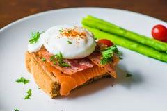 Skjuta in med det tjuvjagade ägget, parma skinka och tomaten Arkivbilder