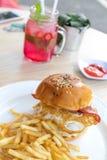 Skjuta in med fega hamburgare-, tomat-, ost-, grönsallat- och fransmansmåfiskar Jordgubbelemonad på en backgorund utanför royaltyfri bild