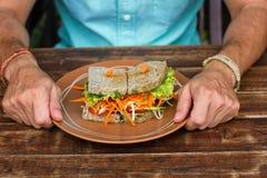 Skjuta in med grönsaker, en vegetarisk smörgås om bröd arkivbilder