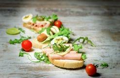 Skjuta in med skinka och smörgåsen med den varma hund-wienerkorven på den lantliga tabellen Arkivfoto