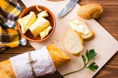 Skjuta in med smör och den skivade bagetten på en skärbräda Royaltyfri Bild