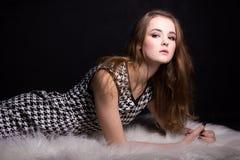 Skjuta modellprovning av en ung nätt flicka Yrkesmässig modell som poserar i studion på en svart bakgrund Arkivbilder
