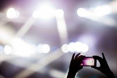 Skjuta videogemet med mobiltelefonen under en konsert royaltyfria foton