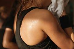 Skjuten detaljidrottshall - svetthud av en kvinnas baksida; snurr aerobi Royaltyfri Fotografi