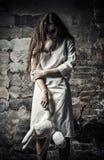 Skjuten fasastil: läskig gigantisk flicka med moppetdockan i händer Arkivfoto