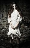 Skjuten fasastil: läskig gigantisk flicka med moppetdockan i händer Royaltyfria Bilder