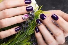 Skjuten härlig manikyr med blommor på kvinnliga fingrar Spikar design Närbild arkivfoton
