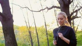 Skjuten Steadicam ultrarapid: En attraktiv ung kvinna gör en morgon att jogga i skogen som solen är glänsande beautifully stock video