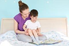 Skjutit av att att bry sig modern på mammaledigheter och den lilla pojken läs sagan för sömn, poserar på säng, siktsfoto, tycker  royaltyfri foto