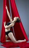 Skjutit av den gulliga kvinnliga dansaren som poserar på flyg- silke Royaltyfri Fotografi