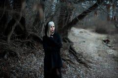 Skjutit av en gotisk kvinna i en skog royaltyfri bild