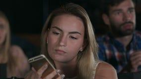 Skjutit av en härlig ung kvinnlig som smsar under filmer på den lokala bion lager videofilmer