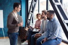 Skjutit av en manlig kontorsarbetare som ger idérik presentation till hans kollegor Affärsman som förklarar affärsplan till fotografering för bildbyråer