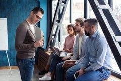 Skjutit av en manlig kontorsarbetare som ger idérik presentation till hans kollegor Affärsman som förklarar affärsplan till royaltyfria bilder