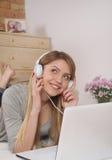 Skjutit av en ung kvinna som lyssnar till musik, medan koppla av hemma Fotografering för Bildbyråer