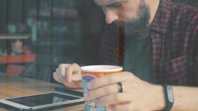 Skjutit av ett mansammanträde i kafé med en smartphone Skjutit till och med kaféshowfönster arkivfilmer
