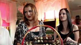Skjutit av fyra kvinnor som gör chokladgodisar arkivfilmer
