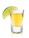 Skjutit av guld- tequila med limefruktskivan Arkivfoto