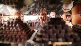 Skjutit av kvinnor som ser på chokladbrända mandlar i skott med reflexion lager videofilmer