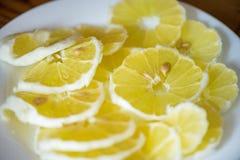 Skjutit av ljusa, gula och sura citronskivor med frö på den vita plattan i mitt av tabellen Royaltyfri Bild