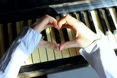 Skjutit av Unidentifiable kvinnliga händer som gör en hjärta Shape över ett piano royaltyfria foton