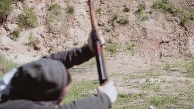 Skjutit från ett prickskyttgevär på ett mål på skjutbanan Skytten faller från stark inverkan arkivfilmer