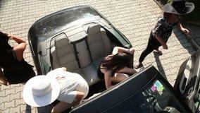 Skjutit från ovannämnt av fyra kvinnor som lämnar bilen lager videofilmer