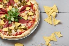 Skjutit i en studio Vegetarisk pizza med frasiga nachos royaltyfri fotografi