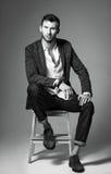 Skjutit studiomode: stående av den stiliga unga mannen i jeans-, skjorta- och omslagssammanträde på bänk svart white royaltyfri fotografi