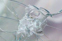 Skjutvapenbullethole på exponeringsglaset från kulorna, sprickabakgrund Royaltyfria Foton