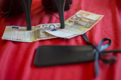 Sköka eller stripteasenummerbegreppet, banknot för euro 50 med könsbestämmer leksaker på röd säng Fotografering för Bildbyråer