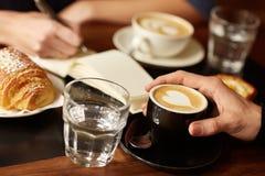 Sklep z kawą stół z rękami, kawą espresso i someone, writing Zdjęcie Stock