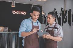 Sklep z kawą właściciel dyskutuje z jego pracownikiem używa pastylkę fotografia royalty free