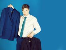 Sklepowego asystenta teraźniejszości kurtki formalny strój na wieszaku zdjęcie royalty free