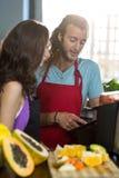 Sklepowi asystenci dyskutuje z cyfrową pastylką przy zdrowie sklepu spożywczego sklepem obrazy royalty free