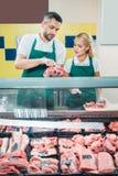 sklepowi asystenci pracuje z świeżym surowym mięsem obrazy royalty free