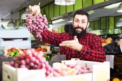 Sklepowy asystent demonstruje winogrona Obraz Royalty Free