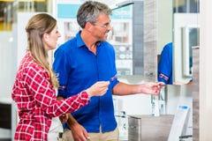 Sklepowy asystent doradza klienta o lavat w narzędzia sklepie Obrazy Royalty Free