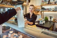 Sklepowy asystent oddaje torbę z sklepami spożywczymi klient obrazy royalty free