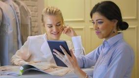 Sklepowy asystent z pastylka laptopem pracuje w sklepie odzieżowym Kobieta butik z ślubnymi sukniami zbiory wideo