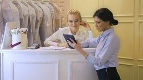 Sklepowy asystent z pastylka laptopem pracuje w sklepie odzieżowym Kobieta butik z ślubnymi sukniami zbiory