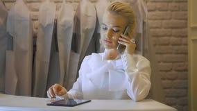 Sklepowy asystent z telefonem pracuje w sklepie odzieżowym Kobieta butik z ślubnymi sukniami zbiory