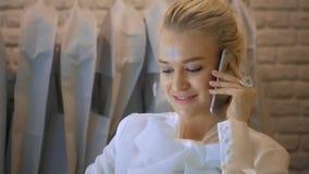 Sklepowy asystent z telefonem pracuje w sklepie odzieżowym Kobieta butik z ślubnymi sukniami zbiory wideo