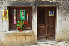 Sklepowy Frontowy okno i drzwi z kwiatami Rovinj Chorwacja i sztuką obrazy stock