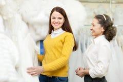 Sklepowy konsultant odziewa pomocy panna młoda wybiera bridal fotografia stock