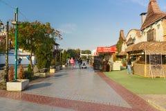 Sklepy i kawiarnie w jesieni na opustoszałym zwyczajnym deptaku Paralia w czarnej dennej kurort wiosce Zdjęcia Royalty Free